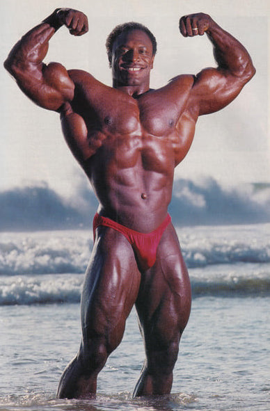 Lee Haney flexing his biceps on the beach in the water